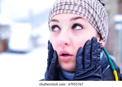 Young woman in winter accessories looking very surprised