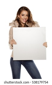young woman in winter jacket holding a blank board for advertisement