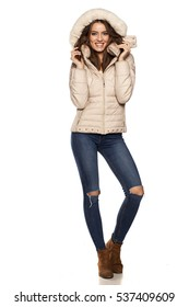 young woman in a winter jacket with hood and jeans on the white background