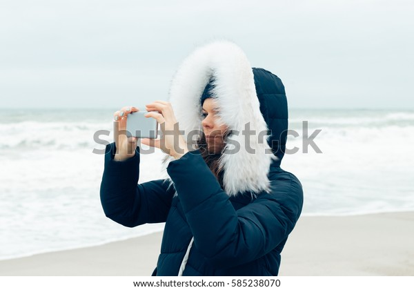 Young woman in a winter jacket with a hood using a mobile phone on the beach, close-up