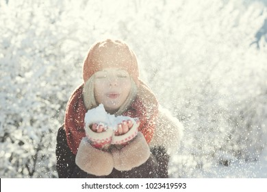 Young woman winter portrait. Beautiful woman blowing snow