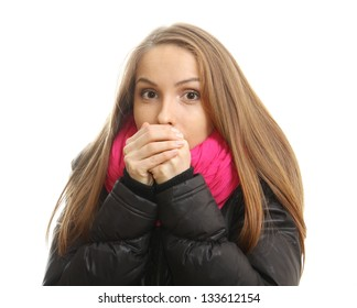 Young woman in winter tries to warm up her hands, isolated