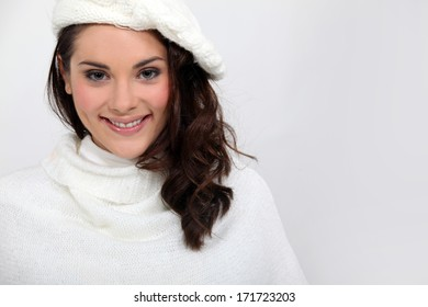 Young woman in a winter white knitted hat and jumper