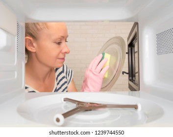 A young woman wipes the microwave after cooking her food.