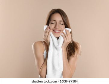 Young woman wiping face with towel on beige background