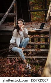 A young woman, with wireless headphones, dressed in ripped jeans and brownish knitwear, is sitting on wooden stairs in front of a cabin in autumn