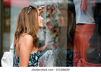 Young woman wistfully looking at the clothes in the shop window