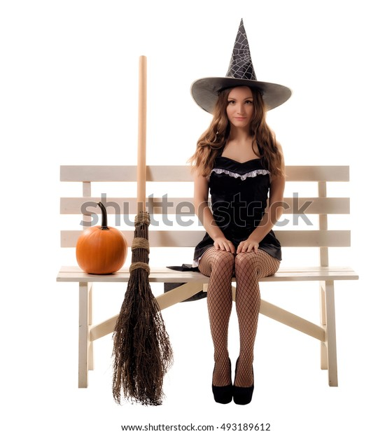 young woman in a witch costume posing in studio