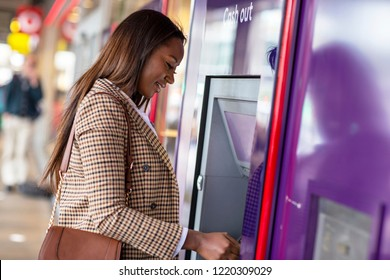 Young woman withdrawing cash from the ATM.