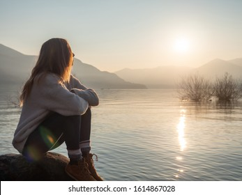 Young woman witting on rock by the lake at sunset looking at view and enjoying the serene atmosphere. Girl relaxing in winter contemplating nature