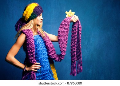young woman in wool scarfs and flower in hand, studio shot
