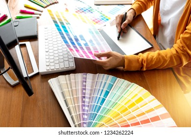 young woman work for graphic design working on wood table with computer tablet electronic pen and color chart