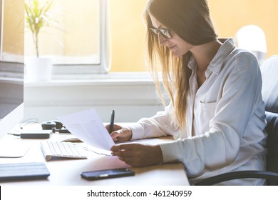 Young woman at work, reading and writing some papers on the desk. Home office or small company situation with real people. She is wearing a shirt and eyeglasses.