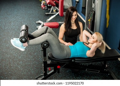 Young woman work0out in fitness gym with her personal coach doing ab intervals