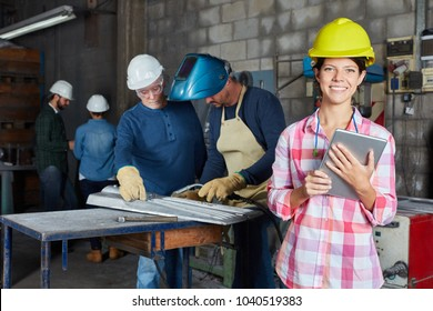 Young woman as worker apprentice or trainee with tablet computer