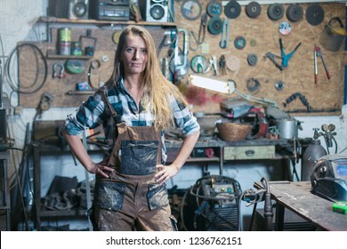 young woman worker in a workshop posing