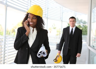 A young woman working as architect on a construction site with coworker in background