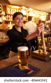 A young woman working behind a bar looking to camera