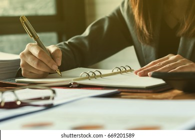 Young woman working in bright office, using laptop, writing notes.