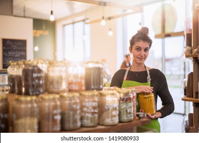 Young woman working in a bulk food store, she puts away the spice jars