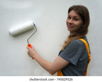 Young woman in working clothes painting a white wall