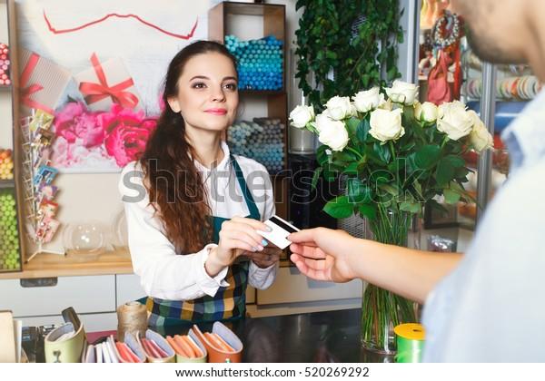 Junge Frau, die als Floristin arbeitet und Kreditkarte an den Kunden übergibt , Mann, der der Verkäuferin eine Kreditkarte übergibt