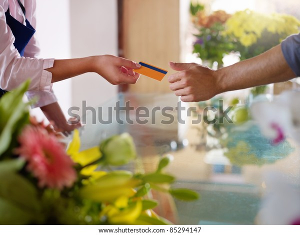Young woman working as florist giving credit card to customer after purchase. Horizontal shape, closeup