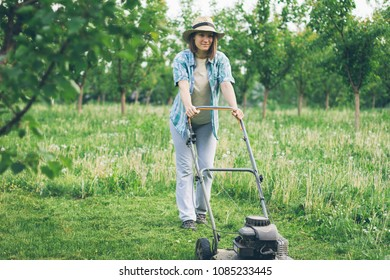 Young woman working in garden gardening trimming grass with lawn mower