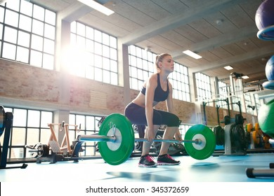 Young woman working hard in the gym. Fit female athlete lifting weights in health club.