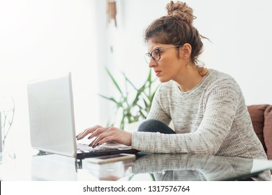Young woman working at her home. She working at lap top