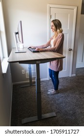 Young woman working at her standing desk in her home office on her computer