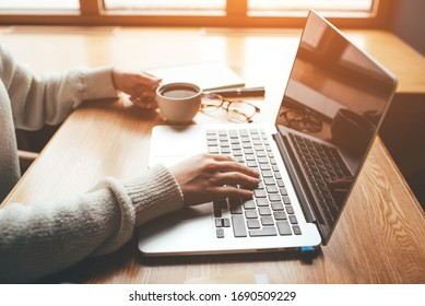 Young woman working in a home office on her laptop computer. Remote work concept.