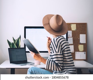 Young woman working at home office. Girl wearing in glasses works with new startup project. Female thinking and writing in planner or diary at workplace of minimalist style with computer.