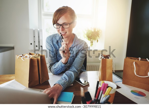 Young Woman Working at Home on her laptop, Small Office