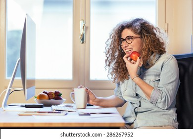 Young woman working at home or in a small office, vintage hipster clothing, curly hair. She is eating some fresh fruits, there is a cup of tea or coffee on the desk with some technological devices.