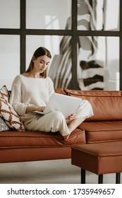 Junge Frau, die zu Hause mit Laptop arbeitet.