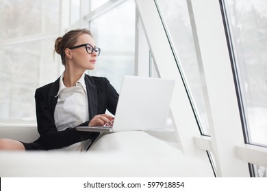 Young woman working at lap top in the office.
