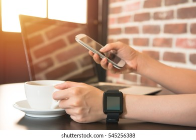 young woman working at laptop with cup of coffee in restaurant. And looking at smartphone. mixed race asian chinese model