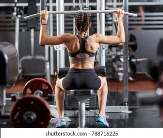 Young woman working at the lat pulldown machine in the gym
