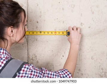 Young woman working with measuring tape in house under reconstruction