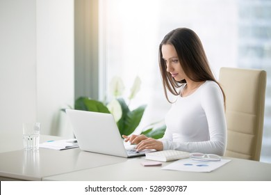 Young woman working at the modern office desk with a laptop, busy with distance learning, tutoring, making online surveys. Lady boss at her workplace. Business success concept