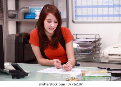 Young woman working in the office of a building firm