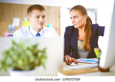 Young woman working in office, sitting at desk. Young woman. Partners
