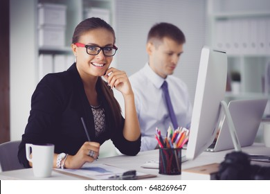 Young woman working in office, sitting at desk with folder