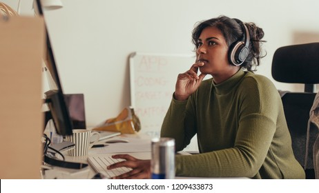 Young woman working on computer in tech startup office. Female programmer sitting at desk and looking away thinking.