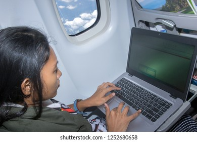 a young woman working on computer while traveling by plane. The passenger of aircraft is looking at the notebook.