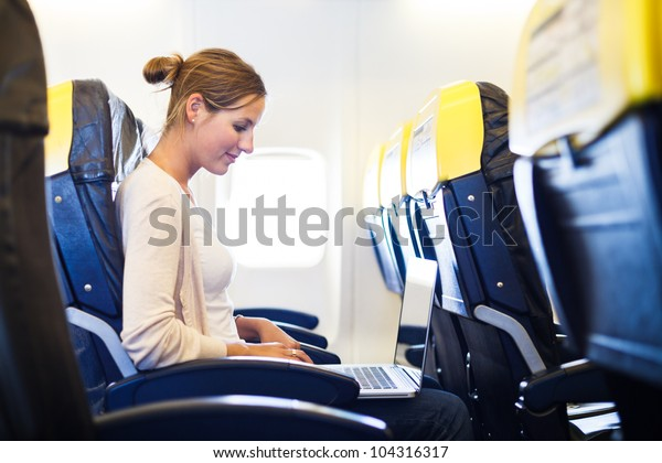 Young woman working on her laptop computer on board of an airplane during the flight