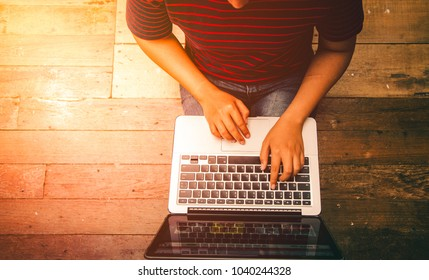 Young woman working on laptop computer while sitting on the wooden floor with sunlight, vintage tone.