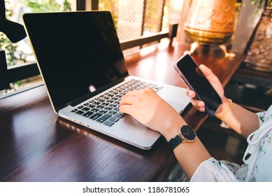 Young woman working on laptop computer on the wooden desk at Coffee shop, vintage tone.Bussiness concept background,