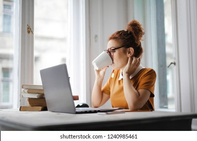 Young woman working on a laptop and drinking coffee.
